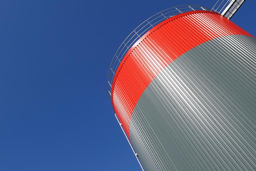 gray and red storage tank against a blue sky