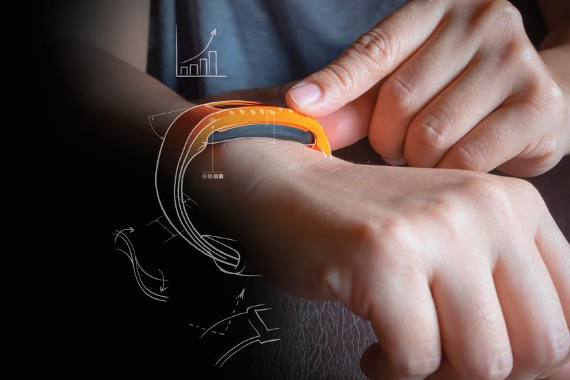 person wearing orange smart device with engineering notes