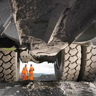 view beneath truck with orange safety workers